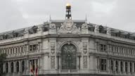 A Spanish national flag flies above the town hall as automobiles drive around Cibeles Square in Madrid Spain on Sunday Oct 20 High angle views a...