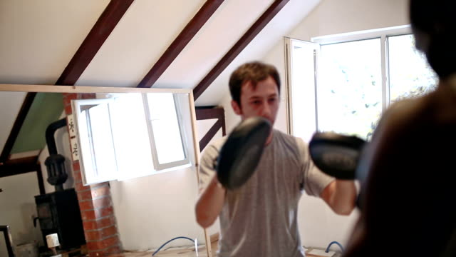 Sparing with partner, punching in punching mitts