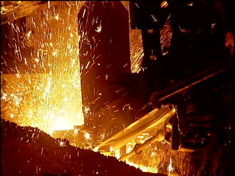 Sparks explode violently around machinery at steel works