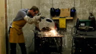 Sparks fly as Caucasian man in metal workshop cuts piece of metal with electric saw