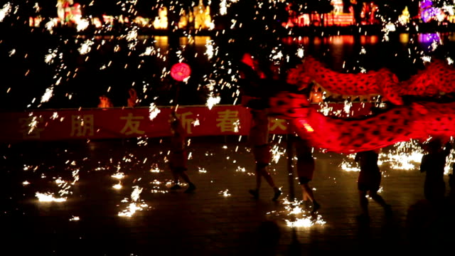 TS Sparks of molten steel dash in all directions.The men perform a dragon dance to celebrate the Spring Festival of China.