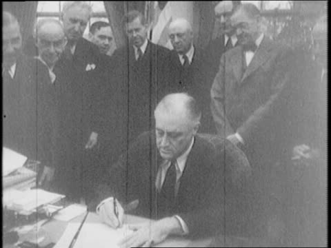 Speaker of the House of Representatives Sam Rayburn signs the war resolution / Vice President Henry Wallace signs / President Franklin D Roosevelt...