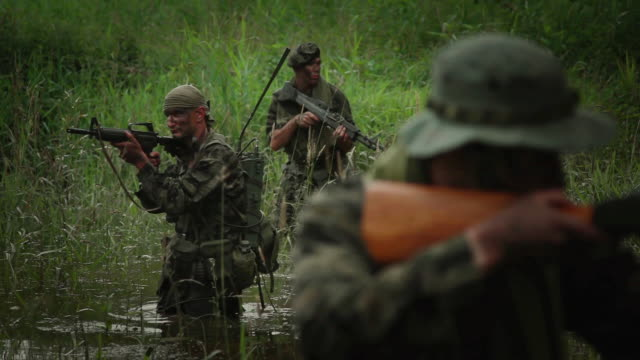 MS R/F U.S. Special Operation Forces soldiers with automatic rifles walking in river in Vietnam war / Jungle, Hue, Vietnam