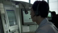 A specialist wears a headset as he watches information flash on a monitor.