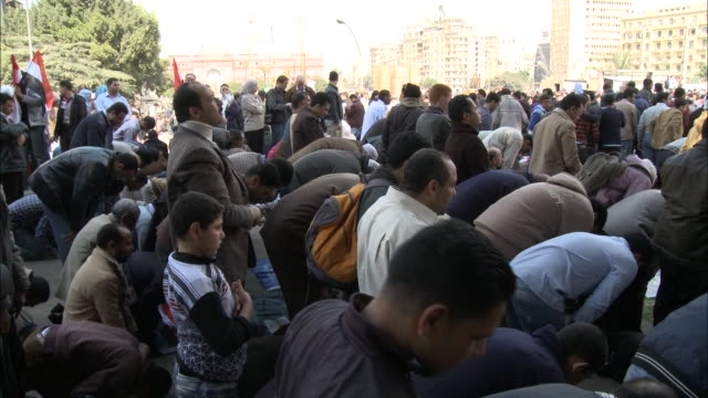 WS Spectators bowing and kneeling in prayer at Mubarak's speech in Tahrir Square / Cairo Egypt