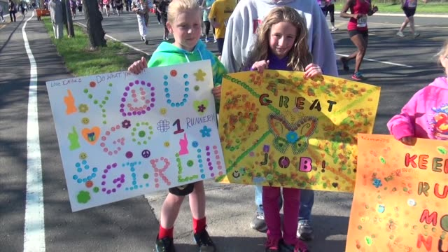 Spectators display signs at sporting event to cheer on participants friends and family