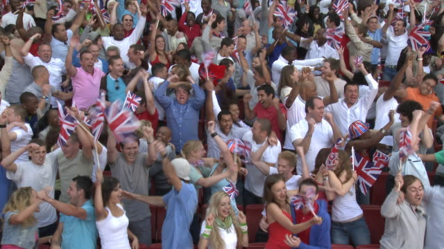 WS Spectators in bleachers jumping and cheering, London, UK