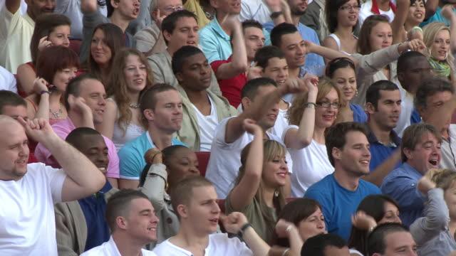 MS ZI PAN Spectators in bleachers waving hands, London, UK