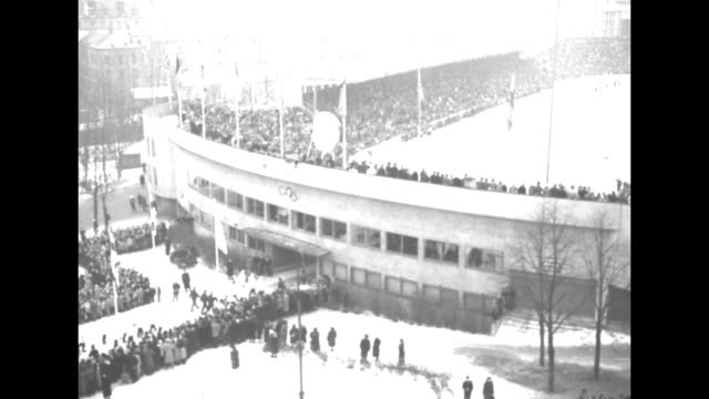 Spectators in stands looking down on ice rink as man carrying burning torch skis by others standing on ice / man at rostrum speaking maybe Oslo mayor...