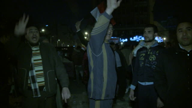 PAN Spectators in Tahrir Square frantically flashing hand signals and yelling while holding an Egyptian flag during Mubarak's speech / Cairo Egypt