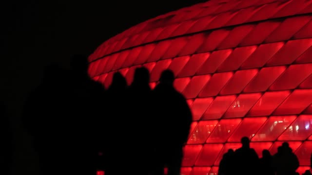 Spectators walk towards the illuminated Allianz Arena for the UEFA Champions League Round of 16 second leg match between Bayern Munchen and Arsenal...