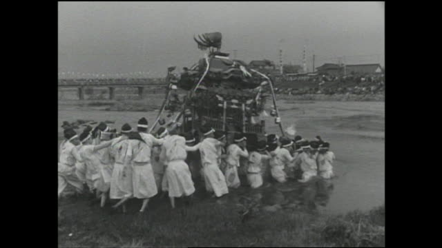 Spectators watch as costumed volunteer porters transport a mikoshi across the Hikosan river.