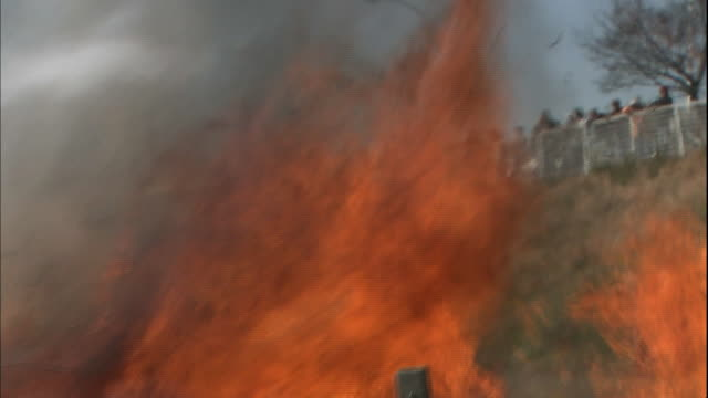 Spectators watch smoke rise from a fire in the Saitama Tajimagahara in Saitama, Japan.