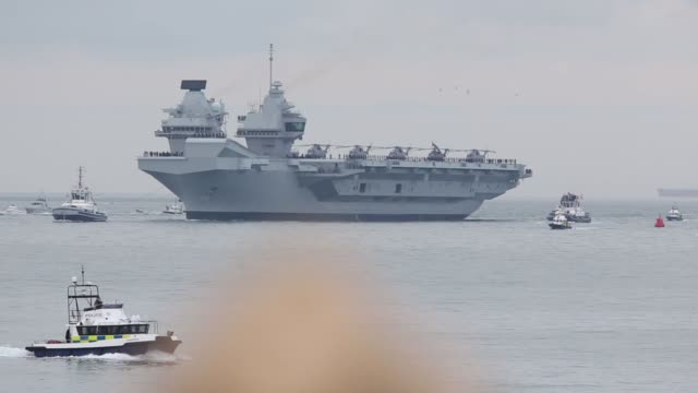 Spectators watch the UK's Royal Navy new aircraft carrier HMS Queen Elizabeth arrives at its home port in Portsmouth UK on Wednesday Aug 16 2017