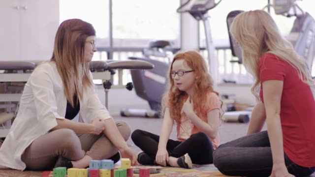 Speech therapist working with a girl and her mother