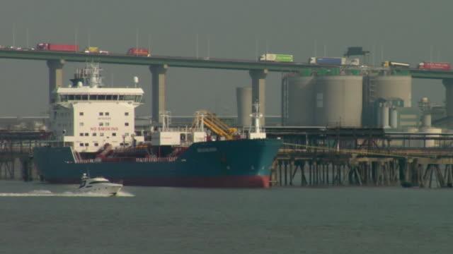 MS, speed boat passing cargo ship docked near Queen Elizabeth II Bridge / Kent, England