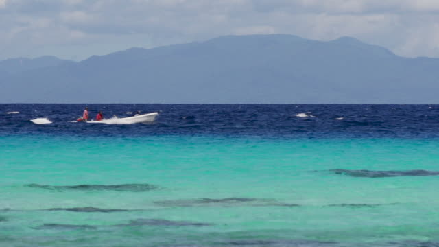 Speed boat through crosses frame in crystal blue water, wide