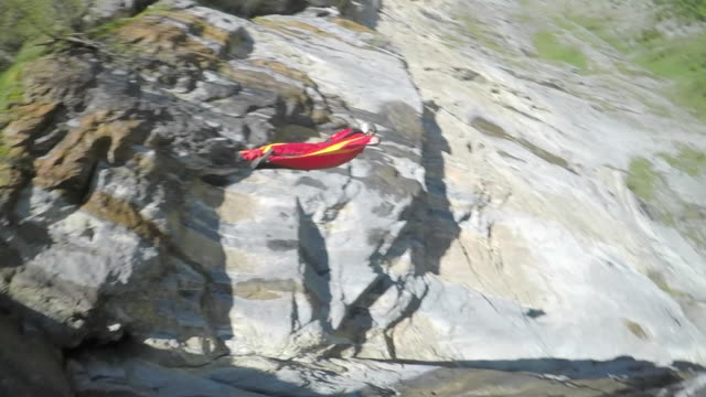 Speed drone view of wingsuit flyer jumping off cliff