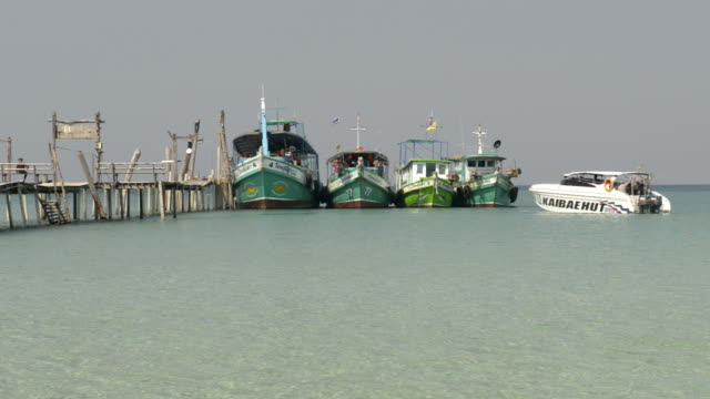 Speedboat leave wooden jetty with excursion ships