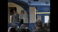 crowd wait / Prince Charles and Princess Diana walk past train on platform and greet official welcoming party / children with flowers / disappointed...