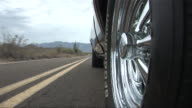 CU Spinning chrome wheel of Pontiac GTO as it drives down desert road/ Scottsdale, Arizona