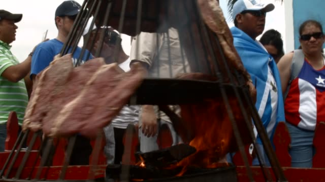 CU A spinning open fire grill at the Calle Ocho festival General clips of the Calle Ocho street festival in the Little Havana neighbourhood of Miami...