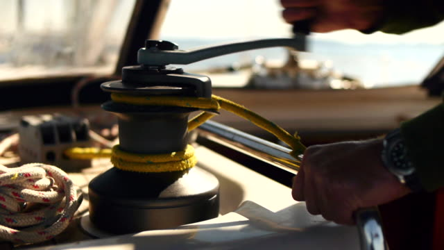 Spinning the winch of a pulley on a sailboat