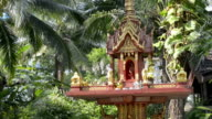Spirit house with palm trees