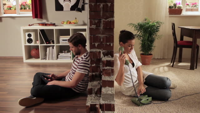 WS Split screen showing couple trying to dial each others at same time  / Berlin, Germany
