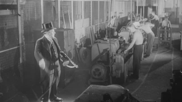 1957 HA Spoof of a taskmaster dressed in top hat and tails, carrying a tommy gun, standing on a crate, and cracking a whip while factory workers feverishly work on their machines / United Kingdom