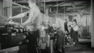 1957 WS Spoof of factory workers at work stations being bestowed with bonuses by an angel winged, tuxedo wearing gentleman who showers the workers with paper bonuses as he skips and leaps along / United Kingdom