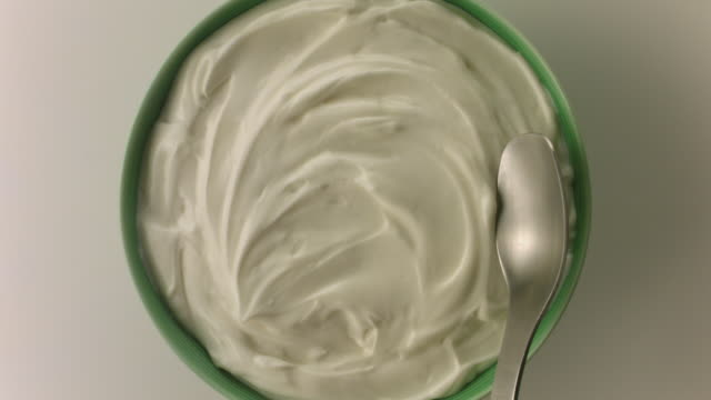 Spoon scoops yogurt from green bowl