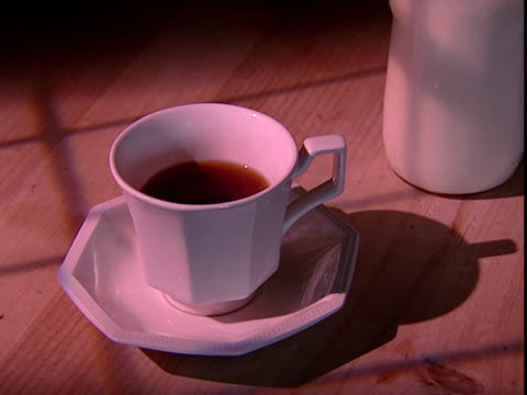 A spoon stirs milk into a cup of tea.