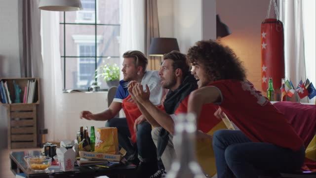 Sport-fans sitzt auf Sofa vor dem Fernseher und jubeln