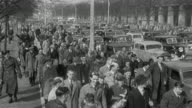 1965 MONTAGE Sports arena packed with cheering spectators, and a street crowded with pedestrians and a traffic jam of automobiles / United Kingdom