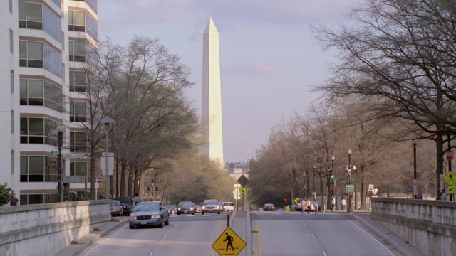 TS A sports cars weaving through traffic then entering an underpass adjacent to the Washington Monument / Washington, D.C., United States