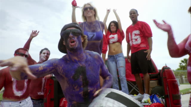 SLO MO MS Sports fan wearing body paint holding keg of beer in air, others cheering, Jacksonville, Florida, USA