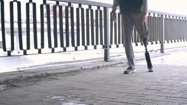 Sporty man with prosthetic leg running outside