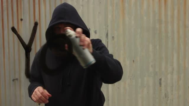 Spraying 'Youth' in Graffiti on glass