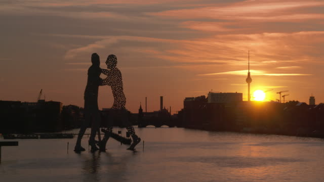 Spree River with Molecule Men, Oberbaum bridge and Berlin television tower at sunset. Spree River, Berlin, Germany.