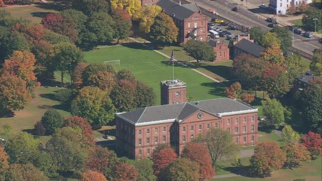 AERIAL Springfield Armory in extensive parkland with fall trees / Springfield, Massachusetts, United States
