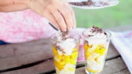 Sprinkling chocolate shavings to top of ice cream and fruit salad