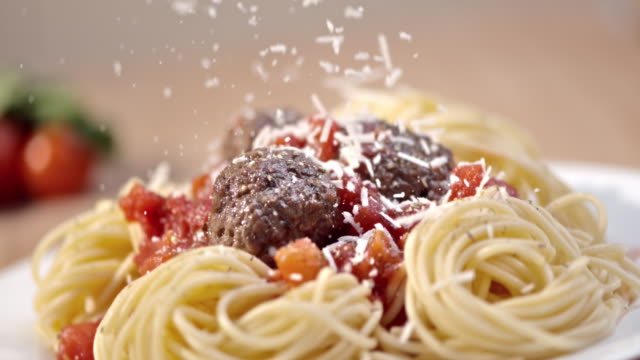 SLO MO Sprinkling parmesan over spaghetti and meatballs