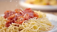 SLO MO sprinkling parmesan over spaghetti with tomato sauce