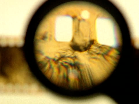 Sprockets of damaged celluloid film strip viewed through magnifying glass 1990s