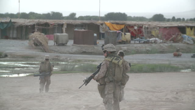A squad of U.S. Marine riflemen have their rifles at the ready as they approach an Afghan village.