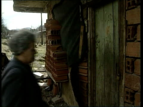 Srebrenica EXT TGV Town TMS Houses one showing bomb damage Advija Sehomerovic along to her old house and finds padlock on door and interview SOT How...