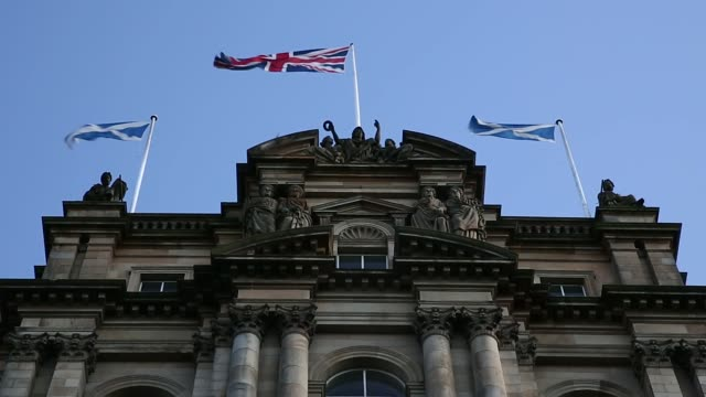 A St Andrews or Saltire flag the national flag of Scotland flies from a flagpole in Edinburgh UK on Saturday Aug 9 The Balmoral Hotel stands in the...