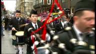 St Patrick's Day parade ENGLAND London EXT Irish wolfhound wearing green coat / People gathered before St Patricks Day parade some wearing hats and...