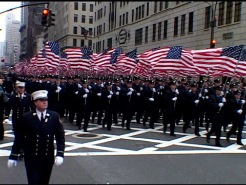 St Patrick's Day Parade Saturday March 16 2002 VS NYFD contingent Firemen march in dress blue uniforms carrying American flags above their heads GOOD...